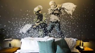 """A Banksy wall painting showing Israeli border policeman and Palestinian in a pillow fight is seen in one of the rooms of the """"The Walled Off Hotel"""" in the West Bank city of Bethlehem, Friday, March 3, 2017"""