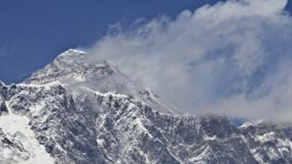This photograph taken on April 20, 2015 shows a view of Mount Everest (C-top) towering over the Nupse-Lohtse massif (foreground) from the village of Tembuche in the Khumbu region of northeastern Nepal.