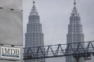 In this Wednesday, 8 July 2015 photo, a 1MDB (1 Malaysia Development Berhad) logo is set against the Petronas Twin Towers at the flagship development site, Tun Razak Exchange in Kuala Lumpur, Malaysia
