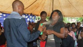A man spraying insecticide in the face of a woman before a congragation.