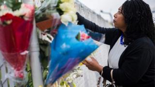 Una mujer deja flores frente al establecimiento donde ocurrió el incendio en Oakland.