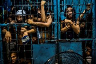 Những người bị bắt giữ đứng sau song sắt tại một đồn cảnh sát ở Manila, Philippines
