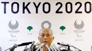 """Tokyo governor Yoichi Masuzoe, sat behind a large number of microphones and in front of a wall display reading """"Tokyo 2010"""", at a news conference in Tokyo on 27 May 2016."""