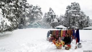 A cloth vender sits by his colourful wares. Snow has settled on the ground around him, and snow covered trees can be seen