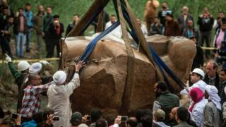 """Egyptian workers excavate the statue, recently discovered by a team of German-Egyptian archeologists, in Cairo""""s Mattarya district on March 13, 2017"""