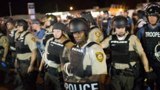 Police stand guard as demonstrators, mark one-year anniversary of shooting of Michael Brown along West Florrisant Street. 10 August 2015 in Ferguson, Missouri