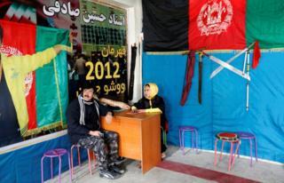 Sima Azimi, a trainer at the Shaolin Wushu club, talks with her father Rahmatullah Azimi, in Kabul, Afghanistan