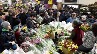 People buying flowers at a market in Moscow