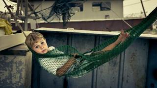 Niño meciéndose en una hamaca.