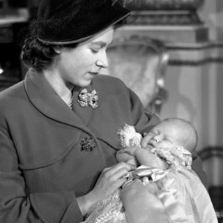 Princess Elizabeth (now Queen Elizabeth II) holding her son Prince Charles after his Christening ceremony in Buckingham Palace
