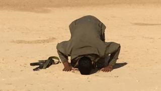 Shia fighter prays during a break in an assault on IS targets in mainly Sunni villages