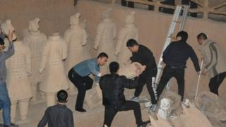 Police dismantling the fake statues