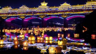 A night scene showing a river covered with hundreds of lanterns, floating under a brightly lit bridge.