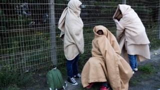 """Migrants, who say they are minors, use blankets to protect themselves from the cold on a street after the dismantlement of the """"Jungle"""" camp in Calais, France, October 27, 2016"""