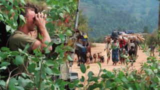French soldier hidden behind a tree looking through binoculars as Rwandan refugees are heading to the refugee camp of Kivumu, western Rwanda. 12 July 1994