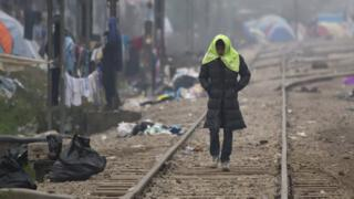 A migrant man walks on railway tracks in Greece