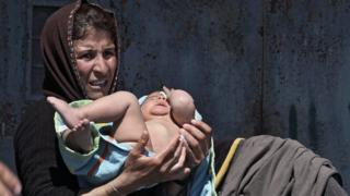 Woman holds her baby in a towel after a bath outside a tent at the port of Piraeus
