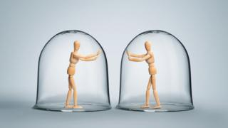Two figures unable to touch each other through glass