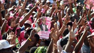 Demonstrators raising hands in the air, and carrying placards of the winner their candidate, Jovenel Moise