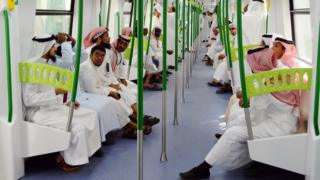 Saudi Arabian men ride on the newly-opened Holy Sites metro light rail in the western Saudi city of Mecca on November 2, 2010.