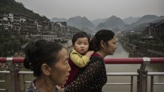 A Chinese woman carries a child across a bridge over the Chishui River