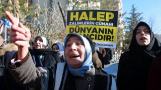 """Protesters in Turkey hold a placard reading """"Aleppo is the world's shame"""" (15 Dec)"""
