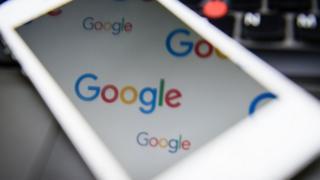 Google logo reflected in a phone screen