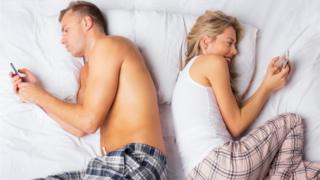 couple in bed on their phones