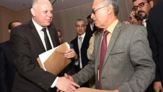 Awad Mohammed Abdul-Sadiq (L), first deputy head of the Tripoli-based General National Congress and Ibrahim Fethi Amish from Libya's internationally recognised House of Representatives exchange signed documents aimed at ending the deadlock in Libya.