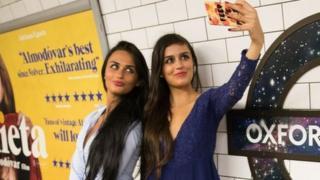 Dos jóvenes se hacen una selfie en el metro de Londres.