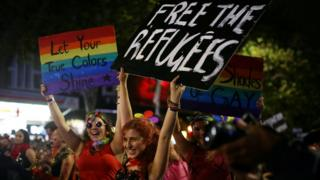 "Marchers with political statements on refugees detained by Australia""s government hold signs during the annual Sydney Gay and Lesbian Mardi Gras parade in Sydney, Australia March 4, 2017. The signs read ""freee the refugees"" and ""let your true colours shine"""