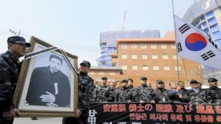 South Korean veterans hold a framed portrait Ahn Jung-Geun during a rally marking the 100th anniversary of his death