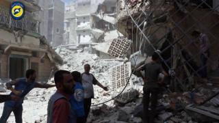 Men stand amid rubble after air strikes in al-Mashhad district in rebel-held eastern Aleppo, Syria (21 September 2016)