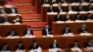 Chinese President Xi Jinping, centre and in focus, surrounded by delegates, out of focus, at a plenary session of the National People's Congress (NPC) at the Great Hall of the People in Beijing, Sunday, March 12, 2017.