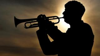 Solder plays last post against backdrop of setting sun