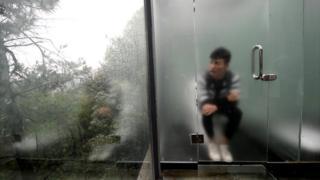 Hombre sentado en un inodoro detrás de una puerta de vidrio ligeramente esmerilado.