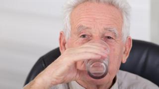 Elderly man drinking water
