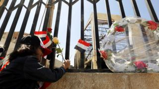 A Yemeni girl puts roses in front of a destroyed funeral hall, a week after Saudi-led airstrikes hit it, during a rally in solidarity and honour of the victims of the 8 October airstrikes, in Sanaa, Yemen, on 15 October 2016