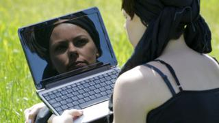 Woman looking at her reflection in computer