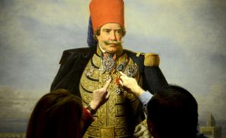 Visitors point at a painting bearing a portrait of former Tunisian ruler from the Husainid Dynasty Muhammad III as-Sadiq during an exhibition at the Ksar Saad Palace in the suburbs of Tunis.