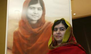 Malala stands in front of the portrait