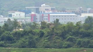 A North Korean guard post (C) stands in front of the inter-Korean industrial complex of Kaesong (background) as seen from the truce village of Panmunjom in the Demilitarized zone dividing the two Koreas on July 22, 2015
