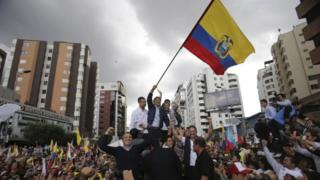 CREO's presidential candidate Guillermo Lasso waves an Ecuadorean national flag, accompanied by his wife Maria de Lourdes Alcivar, his running mate Andres Paez, and surrounded by supporters outside the Electoral National Council, in Quito, Ecuador, Tuesday, Feb. 21, 2017.