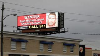 An electronic billboard displays information on a suspect in the killing two police officers in separate shooting attacks in Urbandale and Des Moines, Iowa, U.S., November 2