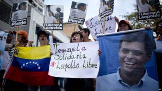 People chant slogans in support of jailed opposition leader Leopoldo Lopez, outside the courthouse in Caracas, Venezuela, Thursday, Sept. 10, 2015.