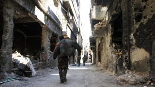 A man walks down a war-damaged street in the Yarmouk refugee camp in Damascus (6 April 2015)