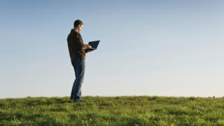 Man using laptop in a field