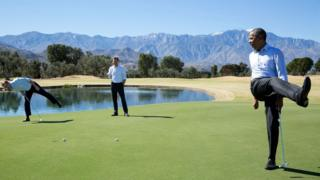 Obama kicks a leg in frustration, while exclaiming, on a putting green with two other players
