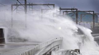 Train passes through waves at Saltcoats in North Ayrshire