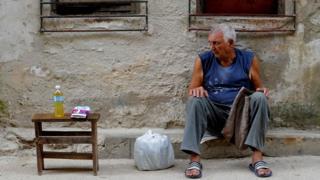 A Cuban elderly man sells goods in a street of Havana, on October 26, 2016